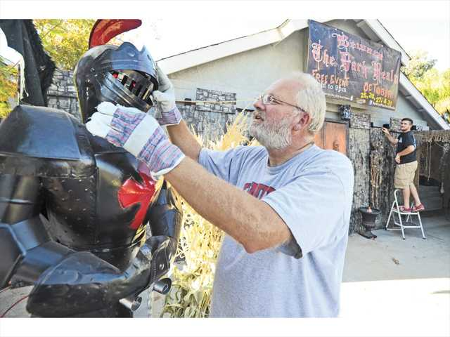 Scott Sivley, left, arranges the armor on the Black Knight in front of his home in Saugus as he and his son Christian put the finishing touches on their haunted house. Photo by Dan Watson.