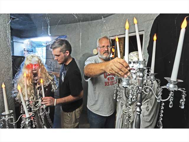 Christian, left, and Scott Sivley set up the props inside the maze in their garage as they prepare for Halloween night. Photo by Dan Watson.