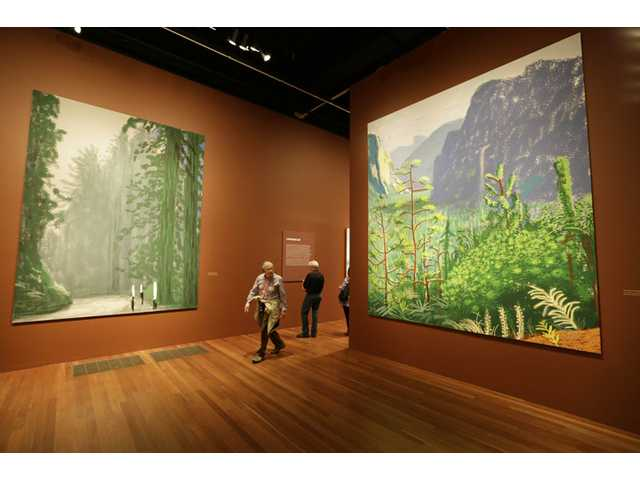 In this photo taken Thursday, a man walks between a pair of 12-foot high views of Yosemite National Park, made by David Hockney using an iPad, at an exhibit in San Francisco.
