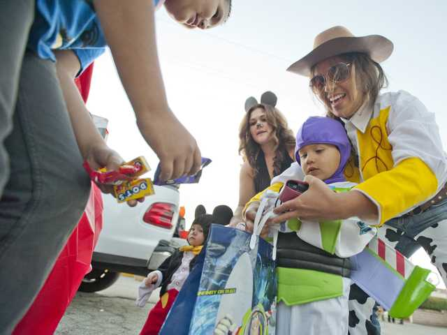 Daniel Ibarra, dressed as Buzz Lightyear from the movie Toy Story, picks out candy with his mother Sally Ibarra at a trunk or treat even at the Valley Community Church in Newhall on Thursday. Photo by Charlie Kaijo.