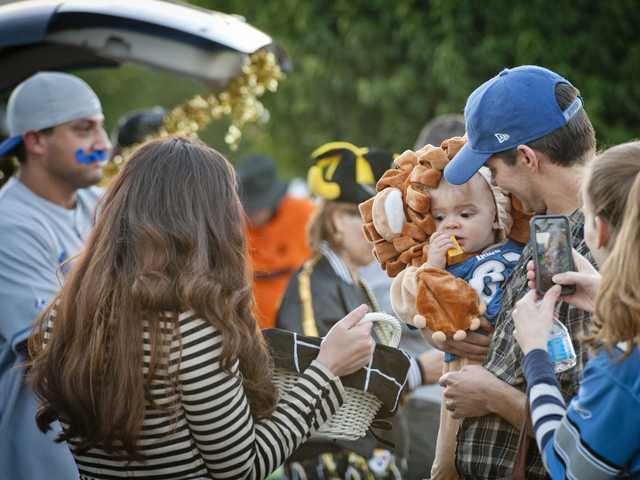 Reed Morrow, dressed as a Detroit Lion, picks out candy at a trunk or treat event at the Valley Community Church in Newhall on Thursday. Photo by Charlie Kaijo.