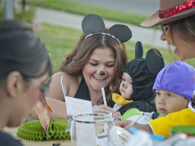 Kristina Garcia and her son, Valentine Sandoval, fill out a raffle ticket for a prize at a trunk or treat event at the Valley Community Church in Newhall on Thursday. Photo by Charlie Kaijo.
