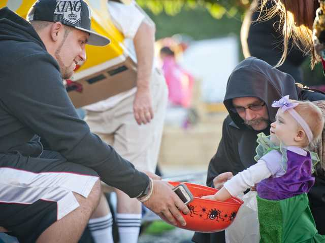 Alicia Curran picks out candy with her father Mike Curran at a trunk or treat event at the Valley Community Church on Thursday. Photo by Charlie Kaijo.