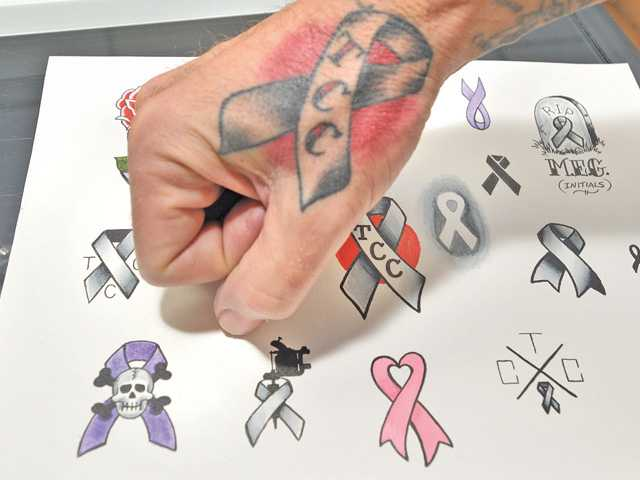 Adam Guyot of Eternal Art Tattoo in Canyon Country displays his Tattoos Cure Cancer tattoo on his wrist and a page of options of the logo that will be available at the Tattoos Cure Cancer fundraiser event, which will occur Sunday.
