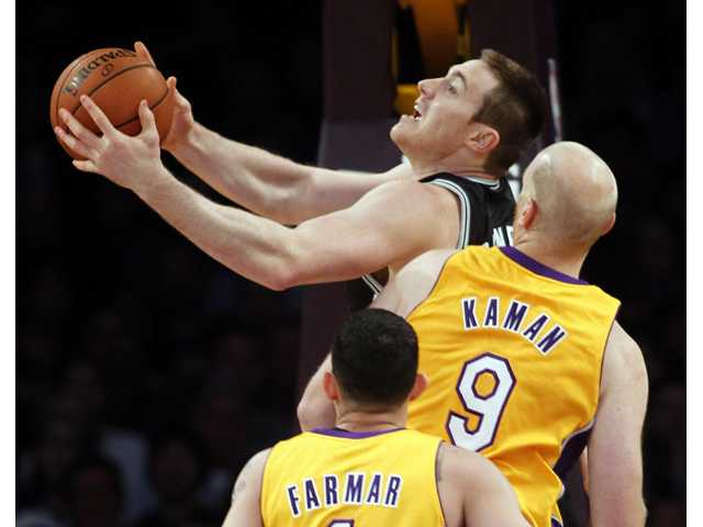 San Antonio Spurs forward Aron Baynes, center, shoots with Los Angeles Lakers center Chris Kaman (9) and Lakers guard Jordan Farmar, below, defending on Friday in Los Angeles.