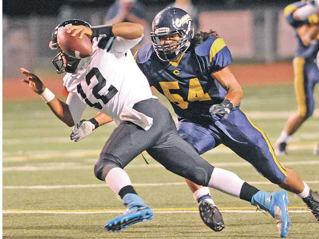 College of the Canyons linebacker Roman Amisone (54) pressures Moorpark College quarterback Nick Davis (12) at COC on Saturday.