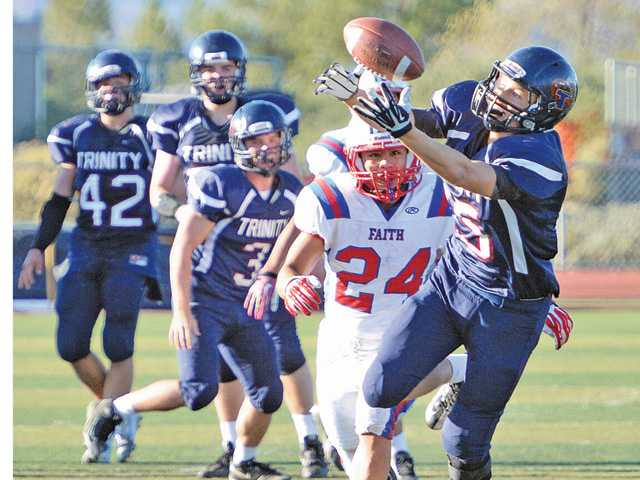 Trinity Classical Academy's Ryan Brooks, right, reaches out to make a catch against Faith Baptist defender Kyle Cadoma (24).