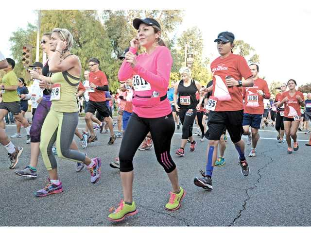 Participants of the full and half marathons take off from the starting point of the 2013 City of Santa Clarita Marathon as they join thousands of runners heading south on McBean Parkway towards Valencia Boulevard on Sunday. Photo by Dan Watson.