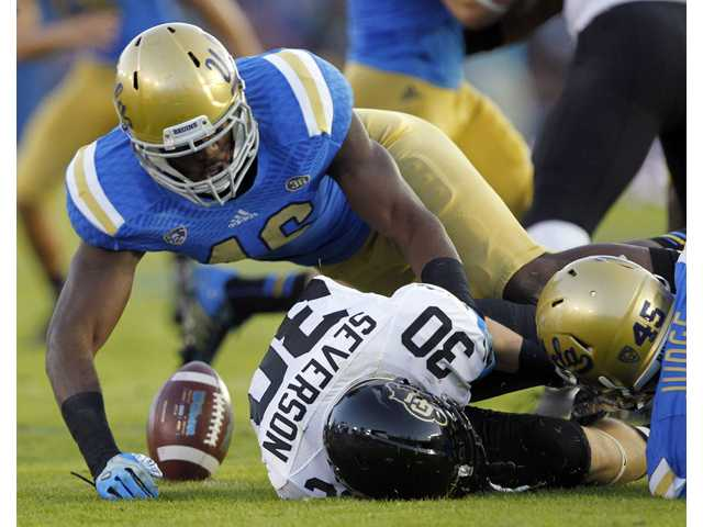 UCLA linebacker Kenny Orjioke, left, and UCLA linebacker Cameron Judge, right, cause Colorado returner Ryan Severson (30) to fumble on a kickoff return on Saturday in Pasadena.