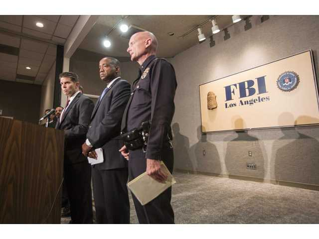 From left to right, FBI Special Agent in Charge David L. Bowdich, United States Attorney Andre Birotte Jr., and Los Angeles Police Department Commander Andrew Smith speak at a press conference on Saturday in Los Angeles.
