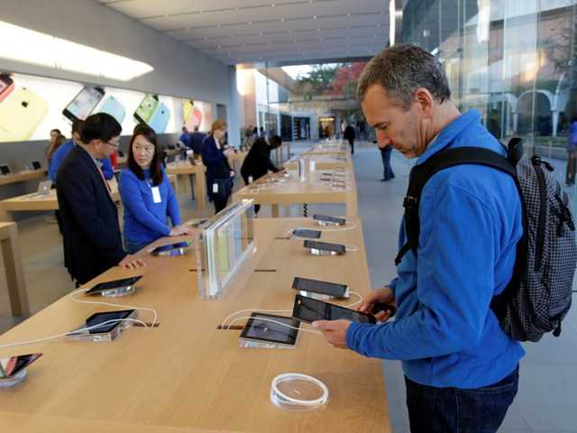 Apple Inc. says it will open a manufacturing plant in a Phoenix suburb that will eventually employ 700 workers. Above, customers look at the new iPad Air on Friday.