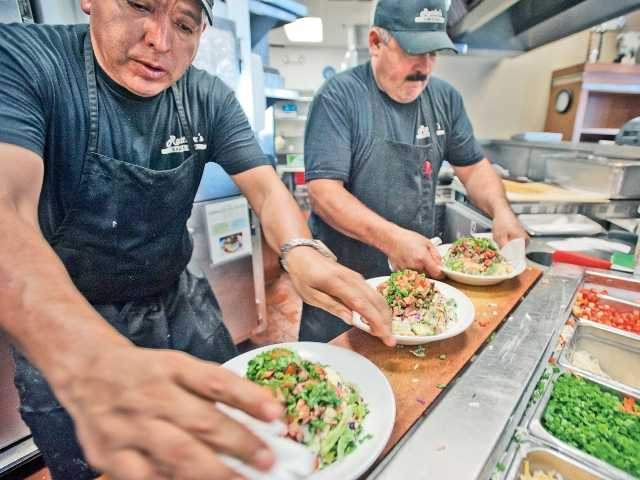 Cornelio Ortis and Martin Castillo prepare chopped lunch salads in the kitchen of Rattler's Bar B Que on Monday.