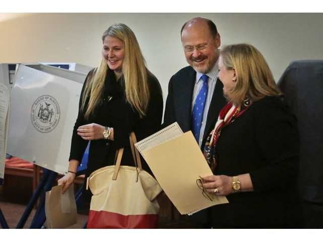 Republican mayoral candidate Joe Lhota, center, his wife Tamra, right, and daughter Kathryn, share a moment of laughter after voting in the general election on Tuesday in the Brooklyn borough of New York.