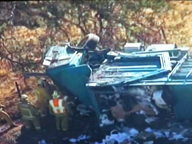 Emergency responders work to free the driver of an overturned trash truck.  KTLA broadcast news screenshot