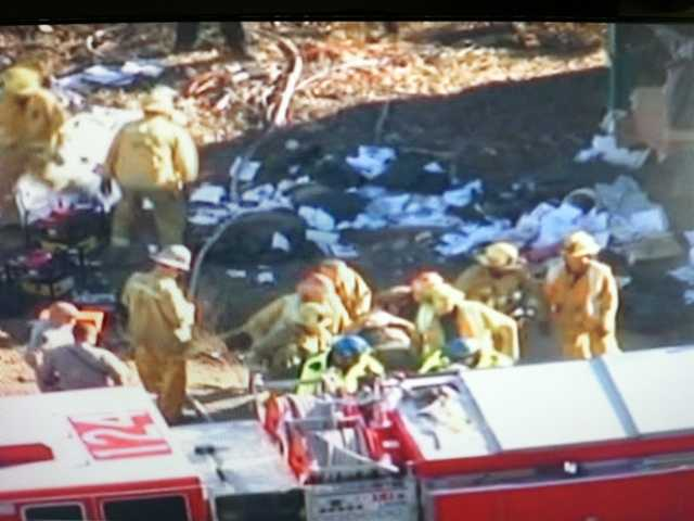The driver is loaded into an ambulance after being freed from his overturned trash truck.  KTLA broadcast news screenshot