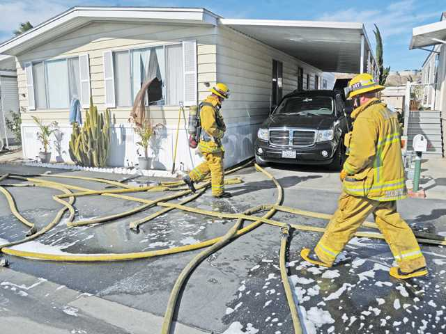 Firefighters mop up after dousing a small blaze inside a mobile home in Canyon Country on Wednesday afternoon. Signal photo by Dan Watson