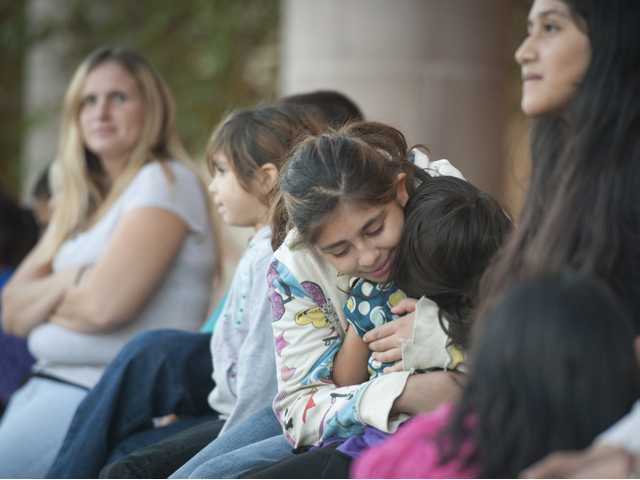 Sixth grader Karla Tovar hugs her sister Mia Tovar while waiting to begin a shopping spree at Khol's department store on Wednesday. Photo by Charlie Kaijo.