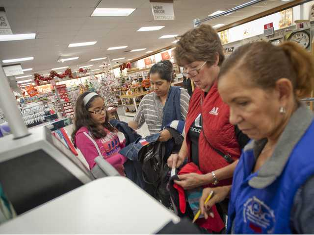 Assistance League members Cheryl Carlson and Carol Lenoir price scan clothes for Josefina Maldonado and her daughter Ashley Martinez at Khol's department store on Wednesday.Photo by Charlie Kaijo.