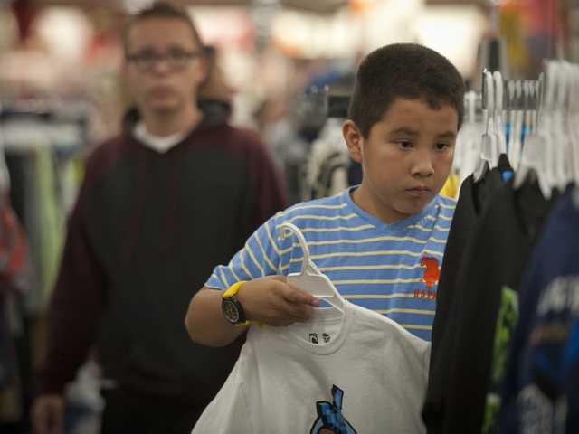 Third grader Fernando Mecos looks for the perfect shirt during the shopping spree. Photo by Charlie Kaijo.