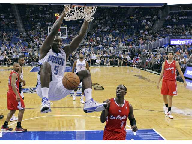 Orlando Magic's Victor Oladipo (5) hangs from the rim after dunking in front of Los Angeles Clippers' Darren Collison (2), Byron Mullens (0) and Willie Green, left.