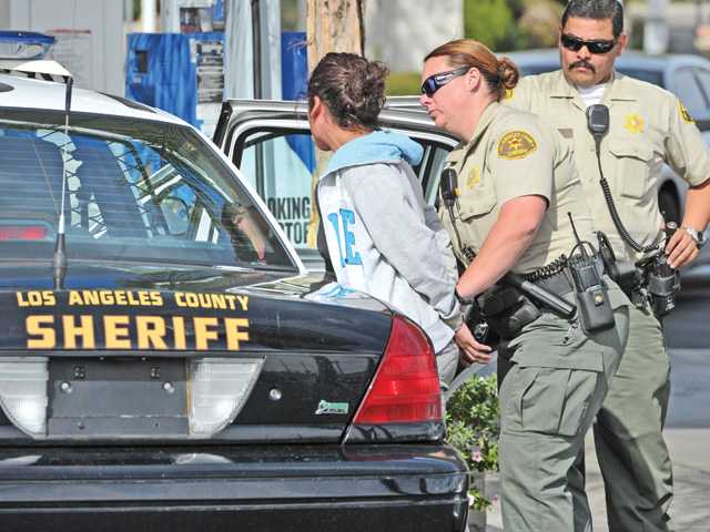 Sheriff's deputies take a woman into custody at a gas station at the corner of The Old Road and Lake Hughes Road in Castaic on Thursday morning.  Signal photo by Dan Watson