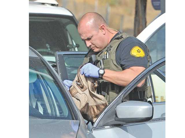 Sheriff's deputies search a bag that was in the silver-colored Honda Accord driven by a woman who was taken into custody at a gas station at the corner of The Old Road and Lake Hughes Road in Castaic on Thursday morning.  Signal photo by Dan Watson
