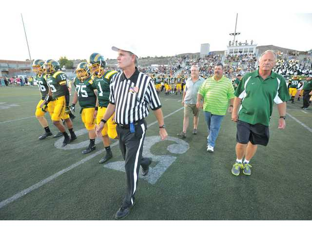 Former Canyon football head coach Harry Welch, far right, walks onto the field at Canyon High with Tony Moore, second from right, and Rick Burton, third from right, who were captains of Canyon's 1983 CIF championship team, before a Canyon High football game on Sept. 7.
