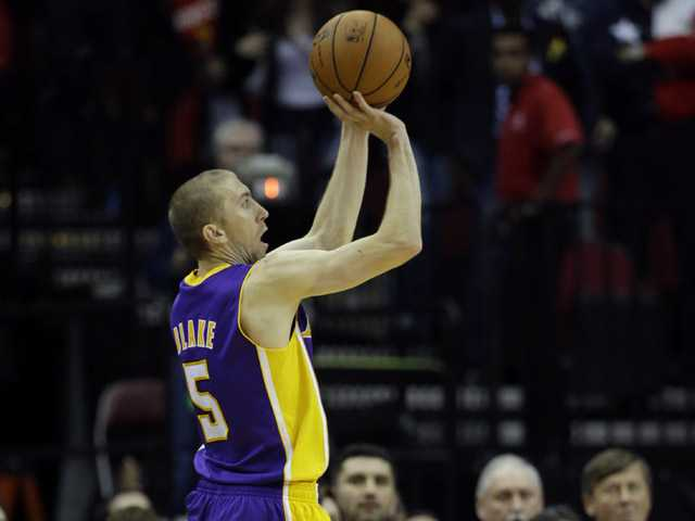 Los Angeles Lakers' Steve Blake (5) shoots his game-winning three-point basket against the Houston Rockets during the closing seconds of the fourth quarter of an NBA basketball game Thursday, Nov. 7, 2013, in Houston. The Lakers won 99-98.