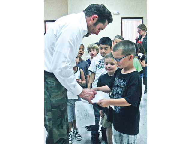 "Students from Highlands Elementary School line up to get Todd White's autograph on their ""Spongebob Squarepants"" drawings after White's art presentation Friday."