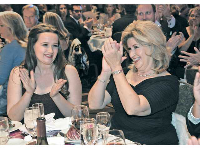 Daughter Katharine, left, applauds as her mother Marlee Lauffer, right, vice president of marketing and communications for Newhall Land, is honored at the Zonta Tribute 2013 Awesome Elegance event at the Hyatt Regency Valencia in Valencia on Friday night.
