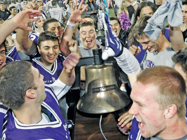 The Valencia High football team celebrates with the Signal Victory Bell after its win against Golden Valley.