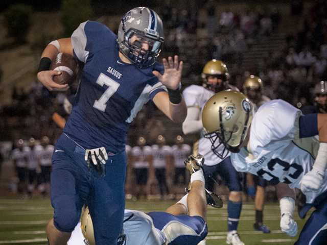 Saugus senior Austin Davenport, left, runs the ball against West Ranch on Friday at College of the Canyons.