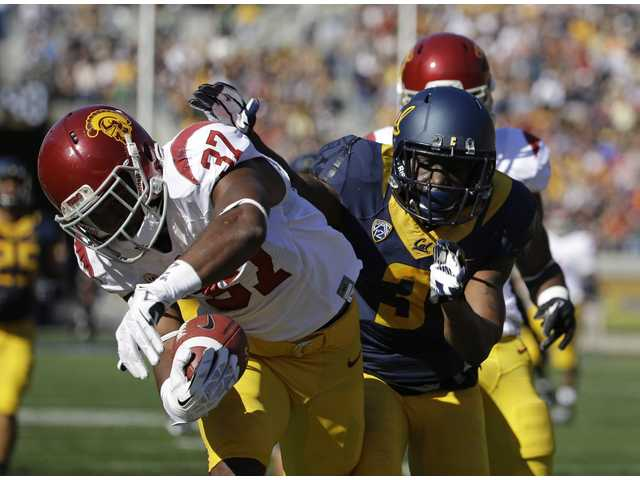 Southern California back Javorius Allen, left, scores a touchdown as California defensive back Kameron Jackson, right, trails during the first quarter.
