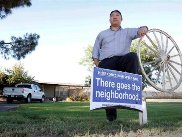 In this photo taken Tuesday, July 16, 2013, high-speed rail opponent Aaron Fukuda poses in front of his Hanford, Calif., home that lies directly in one of the planned train routes.