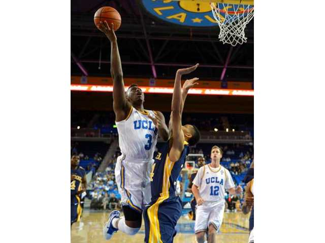 UCLA guard Jordan Adams, left, puts up a shot as Drexel guard Damion Lee, center, defends and forward David Wear looks on during the first half of an NCAA college basketball game Friday, Nov. 8, 2013, in Los Angeles.
