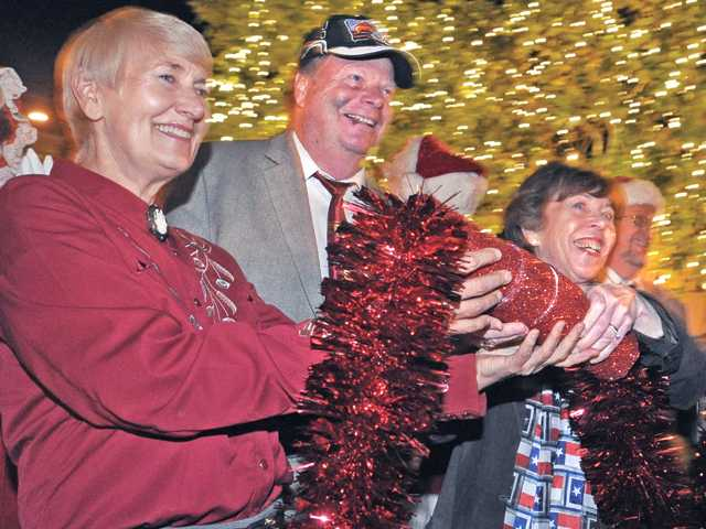 "Santa Clarita City Council members Laurene Weste, Mayor Bob Kellar, Marsha McLean and TimBen Boydston connect the extension cord to light the 23 foot Christmas tree in front of the Old Town Newhall Library and all the lights along Main Street in Newhall during the ""Light Up Main Street"" event on Saturday night in Newhall on Saturday. Signal photo by Dan Watson."