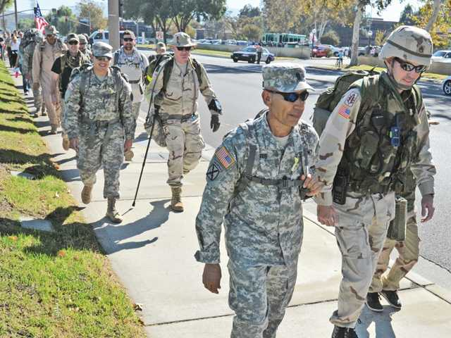 "Command Sergeant Major Alfredo Montes, center, and Santa Clarita Sheriff's deputy and veteran Kevin Duxbury, right, lead a small group on a tactical ""RUCK,"" road march along Magic Mountain Parkway in Valencia on Saturday in support of Santa Clarita Sheriff's Deputy and US Army veteran Luis Gaxiola who is battling a rare form of of cancer.  Signal photo by Dan Watson."