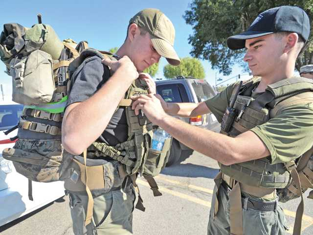 "Trevor Poirier,16, left, and Bailey Palomino, 18, adjust  their packs as they prepare to join a small group on a tactical ""RUCK,"" road march along Magic Mountain Parkway in Valencia on Saturday in support of Santa Clarita Sheriff's Deputy and US Army veteran Luis Gaxiola who is battling a rare form of of cancer. Signal photo by Dan Watson."