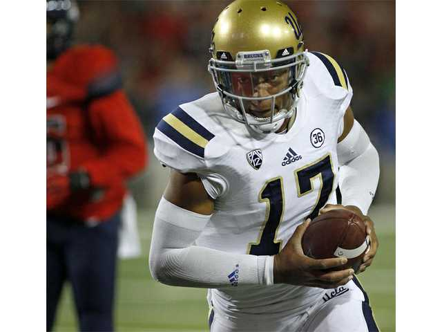 UCLA quarterback Brett Hundley looks into the end zone against Arizona on Saturday in Tucson, Ariz.