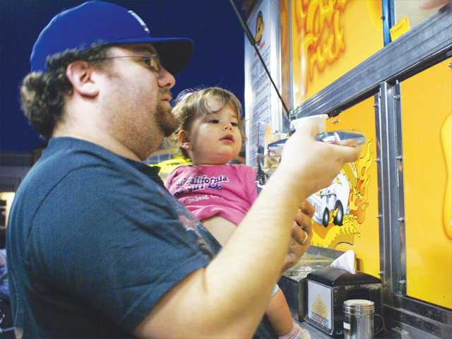 Jason Komen and his daughter Madeline grab some grub from the Grilled Cheese truck during the Second Sundays food truck gathering in Valencia on Sunday. Photo by Jim Holt.