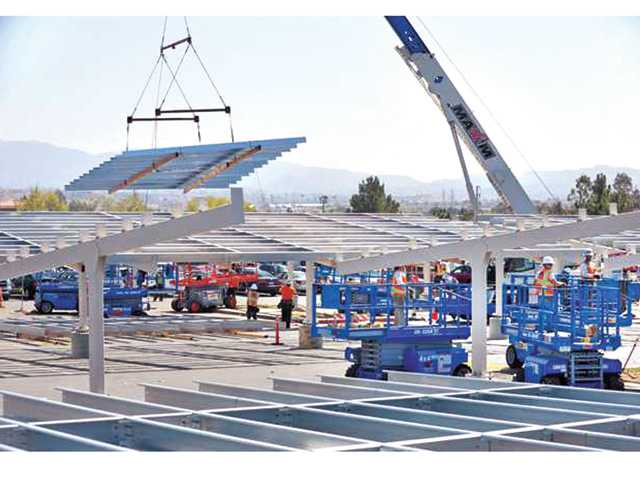 Workers use a crane to lower solar panel supporting frames into place in the Valencia High School parking lot. Signal file photo by Dan Watson.