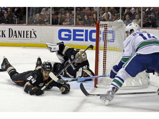 Anaheim Ducks goalie Frederik Andersen (31) and center Daniel Winnik (34) defend as Vancouver Canucks right winger Alexandre Burrows moves in.