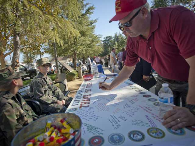 "Scott Mekelburg, retired Army captain, signs and ""thank you"" letter to service members of the military at a Veterans Day Ceremony held at Veterans' Historical Plaza on Monday. Signal photo by Charlie Kaijo"