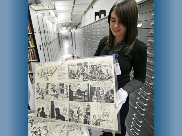 "This October, 2013 photo shows Caitlin McGurk holds up a cartoon titled ""Terry and the Pirates"" by Milton Caniff at the Billy Ireland Cartoon Library & Museum in Columbus, Ohio."