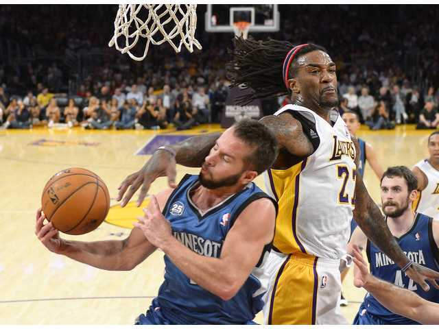 Minnesota Timberwolves guard Jose Barea, puts up a shot as Los Angeles Lakers center Jordan Hill defends during the first half.