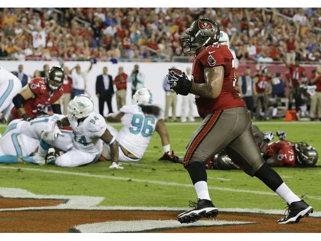 Tampa Bay Buccaneers tackle Donald Penn, right, catches a 1-yard pass for a touchdown against the Miami Dolphins in Tampa, Fla. on Monday.