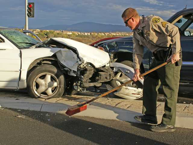 Santa Clarita Valley sheriff's deputy Robert Mahoney sweeps up broken glass after a three-vehicle crash on Bouquet Canyon Road on Tuesday. Photo by Jim Holt.