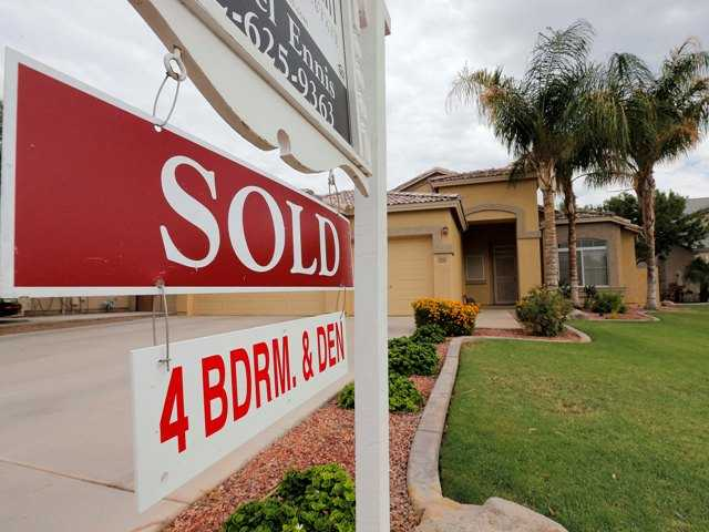 Home sales and prices were lukewarm in October. Above, a used home is listed as sold, in Gilbert, Arizona in August.