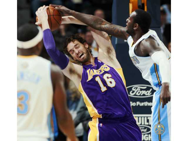 Lakers power forward Pau Gasol pulls down a rebound against Nuggets defenders on Tuesday.