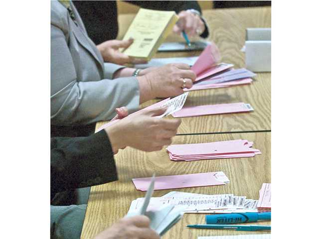 City employee volunteers prepare ballots for the official count at City Council Chambers during the April 2012 election. Signal file photo